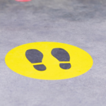 Pavement with a yellow circle with footprints in the middle