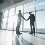 Two business men in an office building shaking hands